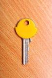 Alloggi la chiave con i cappucci gialli dei cappotti della plastica sulla tavola Fotografie Stock