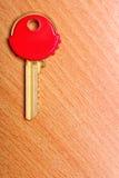Alloggi la chiave con i cappucci rossi dei cappotti della plastica sulla tavola Fotografia Stock