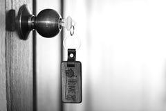 Alloggi la chiave con l'anello portachiavi domestico in buco della serratura, concetto della proprietà Immagine Stock Libera da Diritti