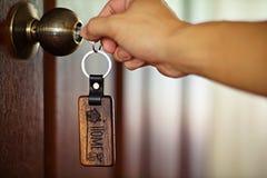 Alloggi la chiave con l'anello portachiavi domestico in buco della serratura, concetto della proprietà Fotografia Stock Libera da Diritti