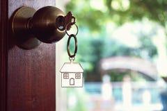 Alloggi la chiave con l'anello portachiavi domestico in buco della serratura, concetto della proprietà Immagine Stock