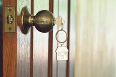 Alloggi la chiave con l'anello portachiavi domestico in buco della serratura, concetto della proprietà Fotografia Stock