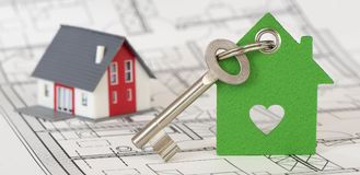 Alloggi la chiave con la casa di modello sopra il piano della costruzione Fotografia Stock