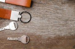 Alloggi la chiave con la catena chiave di cuoio su fondo di legno Fotografia Stock Libera da Diritti