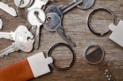 Alloggi la chiave con la catena chiave di cuoio su fondo di legno Immagine Stock