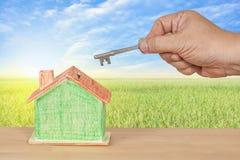 Alloggi la chiave con una casa di modello miniatura su paesaggio Immagine Stock Libera da Diritti