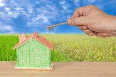 Alloggi la chiave con una casa di modello miniatura su paesaggio Immagini Stock