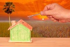 Alloggi la chiave con una casa di modello miniatura su paesaggio Fotografia Stock