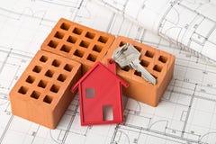 Alloggi la chiave della porta con il pendente rosso ed i mattoni della catena chiave della casa sui Bu Immagini Stock
