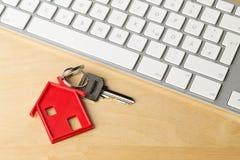 Alloggi la chiave della porta con il pendente rosso ed il tasto del computer della catena chiave della casa Immagini Stock Libere da Diritti