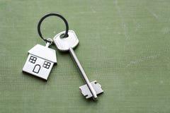 Alloggi la chiave e il keychain sotto forma di case si trova su tessuto Concetto per il bene immobile, l'ipoteca, la casa commove Fotografia Stock