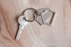 Alloggi la chiave e il keychain sotto forma di case si trova sui bordi di legno Concetto per il bene immobile, ipoteca, casa comm Fotografia Stock Libera da Diritti