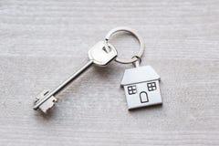 Alloggi la chiave e il keychain sotto forma di case si trova sui bordi di legno Concetto per il bene immobile, ipoteca, casa comm Immagini Stock Libere da Diritti