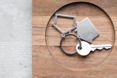 Alloggi la chiave e il keychain sotto forma di case si trova sui bordi di legno Concetto per il bene immobile, ipoteca, casa comm Fotografie Stock