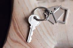 Alloggi la chiave e il keychain sotto forma di case si trova sui bordi di legno Concetto per il bene immobile, ipoteca, casa comm Fotografia Stock