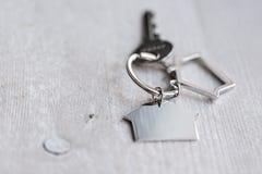 Alloggi la chiave e il keychain sotto forma di case si trova sui bordi di legno Concetto per il bene immobile, ipoteca, casa comm Immagini Stock