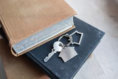 Alloggi la chiave e il keychain sotto forma di case si trova sui libri Concetto per il bene immobile, l'ipoteca, la casa commoven Immagine Stock