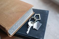 Alloggi la chiave e il keychain sotto forma di case si trova sui libri Concetto per il bene immobile, l'ipoteca, la casa commoven Immagini Stock Libere da Diritti