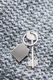 Alloggi la chiave e il keychain sotto forma di case si trova sul tessuto tricottato della lana Concetto per il bene immobile, ipo Immagine Stock