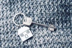 Alloggi la chiave e il keychain sotto forma di case si trova sul tessuto tricottato della lana Concetto per il bene immobile, ipo Immagine Stock Libera da Diritti