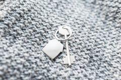 Alloggi la chiave e il keychain sotto forma di case si trova sul tessuto tricottato della lana Concetto per il bene immobile, ipo Immagini Stock