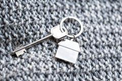 Alloggi la chiave e il keychain sotto forma di case si trova sul tessuto tricottato della lana Concetto per il bene immobile, ipo Fotografia Stock Libera da Diritti