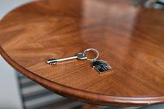 Alloggi la chiave e il keychain sotto forma di case si trova sulla tavola di legno Concetto per il bene immobile, ipoteca, casa c Immagine Stock