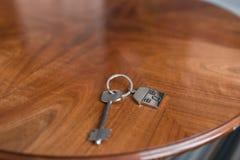Alloggi la chiave e il keychain sotto forma di case si trova sulla tavola di legno Concetto per il bene immobile, ipoteca, casa c Fotografie Stock Libere da Diritti