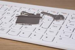 Alloggi la chiave e metal l'etichetta che si trova su una tastiera Fotografie Stock Libere da Diritti