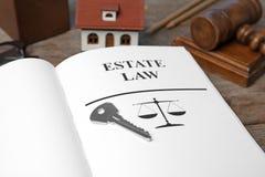 Alloggi la chiave ed il libro aperto con LEGGE di parole PROPRIETÀ sulla tavola, primo piano Fotografia Stock Libera da Diritti