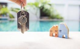 Alloggi la chiave sopra la casa miniatura vaga sul bordo della piscina Immagine Stock Libera da Diritti