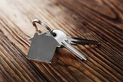 Alloggi la chiave su keychain a forma di casa sulle tavole di pavimento di legno Fotografie Stock