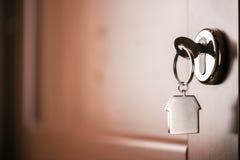 Alloggi la chiave su un anello portachiavi d'argento a forma di casa nella serratura di un entr Immagini Stock