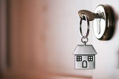 Alloggi la chiave su un anello portachiavi d'argento a forma di casa nella serratura di un entr Fotografie Stock