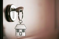 Alloggi la chiave su un anello portachiavi d'argento a forma di casa nella serratura di un entr Immagini Stock Libere da Diritti