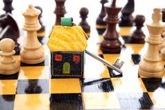 Alloggi la chiave sulla scacchiera - concetto di forma del bene immobile Immagine Stock Libera da Diritti