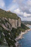 Alloggi la condizione sull'orlo di grande scogliera in Afionas Corfù Grecia Fotografia Stock