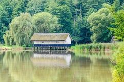 Alloggi la configurazione sull'acqua, tetto della paglia, vicino al lago ed alla foresta verde Fotografia Stock Libera da Diritti