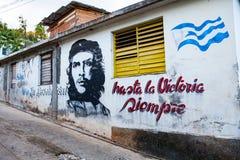 Alloggi la facciata in Baracoa con la propaganda ed il Ch comunisti dipinti Fotografie Stock