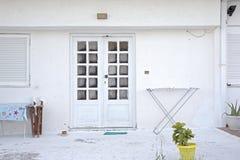 Alloggi la facciata con i vasi da fiori, l'essiccatore dello scaffale dell'abbigliamento, le sedie e la tavola Fotografia Stock