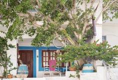 Alloggi la facciata con i vasi da fiori, le sedie e l'albero Fotografie Stock Libere da Diritti