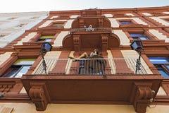 Alloggi la facciata con il balcone ed il distretto leggero delle bambole in rosso vicino alla stazione ferroviaria principale Fra Fotografia Stock