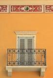Alloggi la facciata con il balcone, gli otturatori chiusi e lo stucco ornamentale Fotografia Stock Libera da Diritti