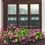 Alloggi la facciata con la finestra ed i fiori in alpi Fotografia Stock
