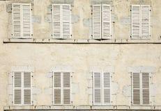 Alloggi la facciata con otto otturatori chiusi nel bianco Fotografie Stock