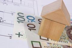 Alloggi la forma dei blocchi di legno e lucidi la valuta sul disegno di costruzione Immagine Stock Libera da Diritti