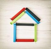 Alloggi la forma delle clip variopinte della borsa sui precedenti di legno Immagine Stock