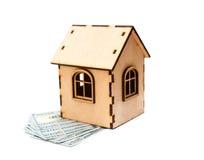 Alloggi la forma fatta dei blocchi di legno e del dollaro di valute che si trova su costruzione elettrica Fotografie Stock Libere da Diritti
