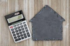 Alloggi la lavagna a forma di con il calcolatore su legno stagionato Fotografie Stock Libere da Diritti