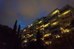 Alloggi la notte con le luci sopra e l'illuminazione viola del cielo nuvoloso Immagine Stock